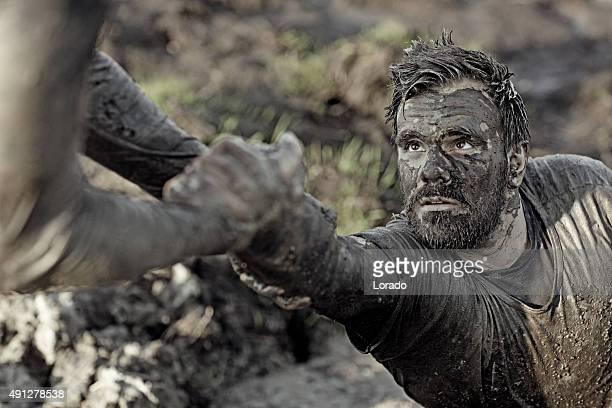 Uomo aiutando il suo amico con alzano dal fango