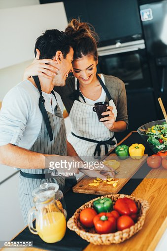 Man helping his girlfriend with the cooking : Stock Photo
