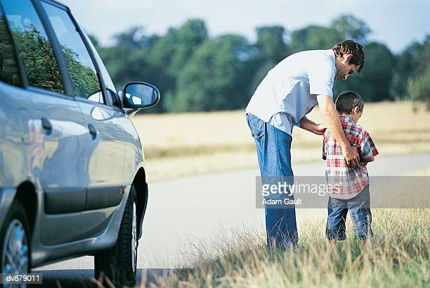 Man Helping His Son To Urinate at the Side of the Road