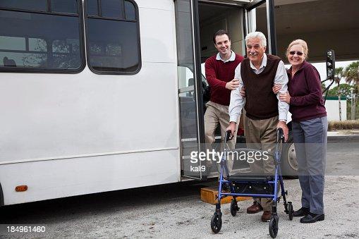 Man helping senior couple outside shuttle bus