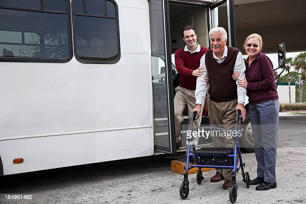 Homme aider senior couple à l'extérieur de la navette