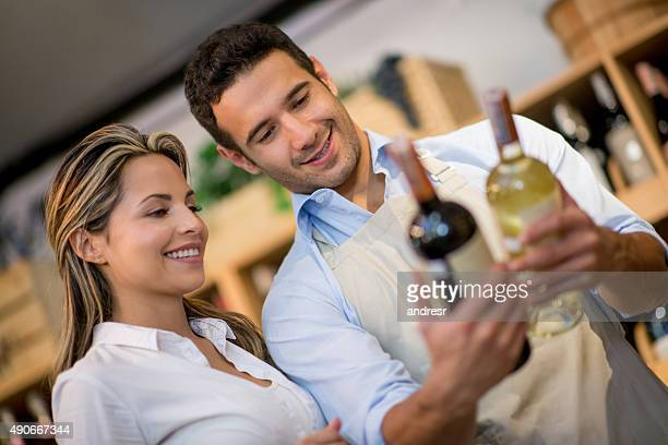 Man helping woman at the supermarket buying wine