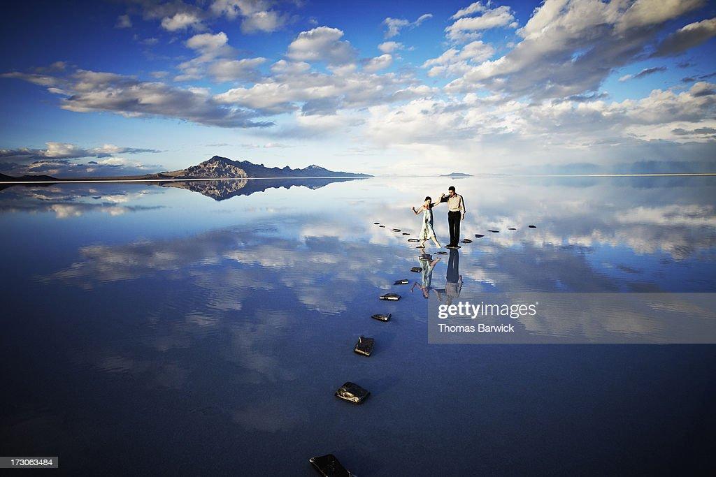 Man helping woman balance on stone pathway in lake