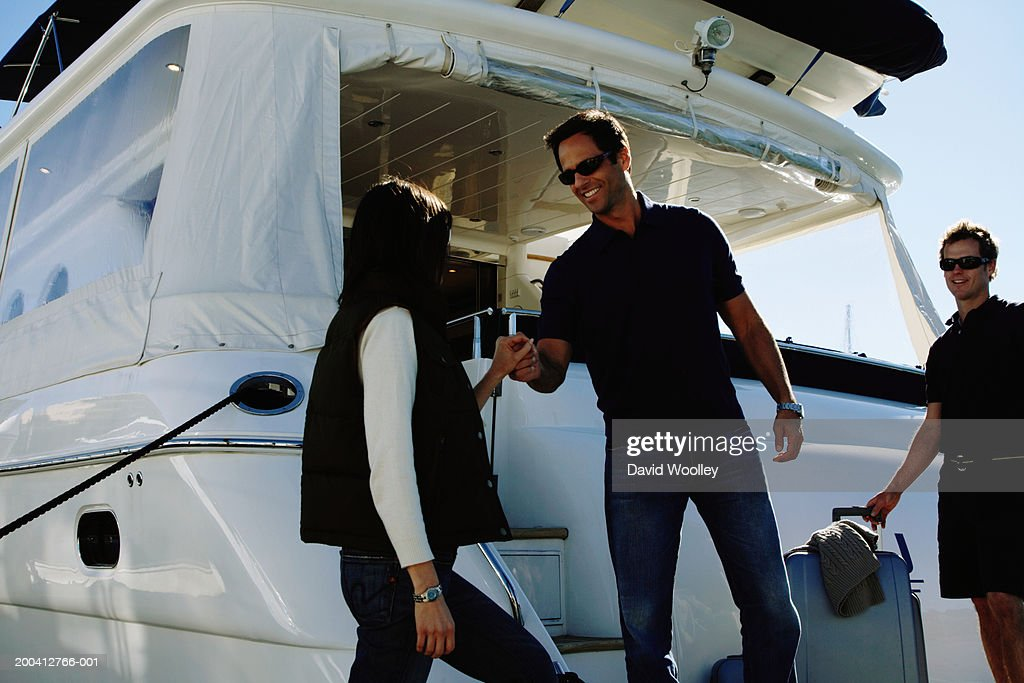 Man helping woman board yacht, smiling, male crew member in background : Stock Photo