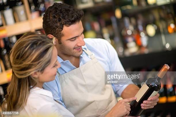 Man helping woman buy a bottle of wine