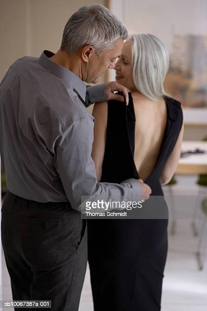 Man helping woman do up dress, rear view