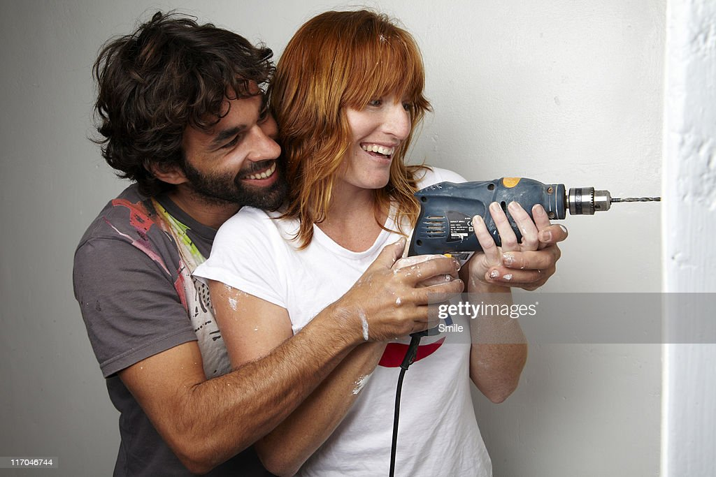 Man helping woman drill hole in wall