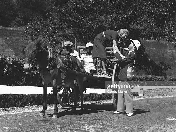 Man helping woman getting out of horse cart, (B&W)