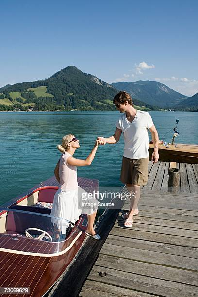 Mann helfen Frau auf einem Boot