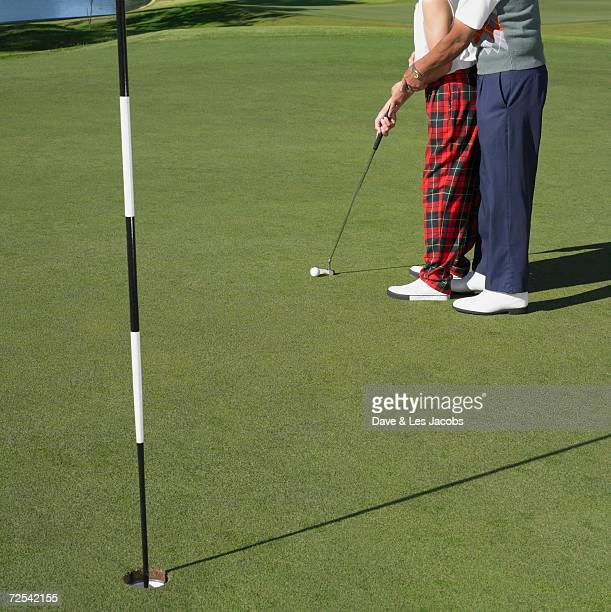 Man helping woman putt on golf course