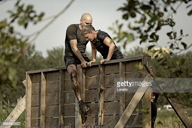 man helping woman to climb wooden wall obstacle