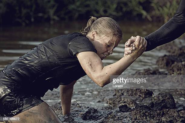 man helping woman to get out of mud