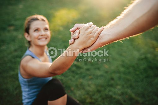 Man helping woman to stand up : Stock Photo