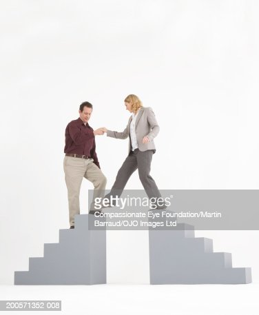 Man helping woman to step over from top of one staircase to other