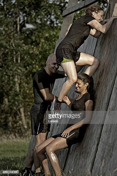 man helping women to climb wooden wall obstacle