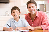Man helping young boy in kitchen doing homework and smiling To Camera