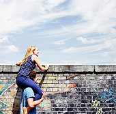 Man helping young woman look over wall.