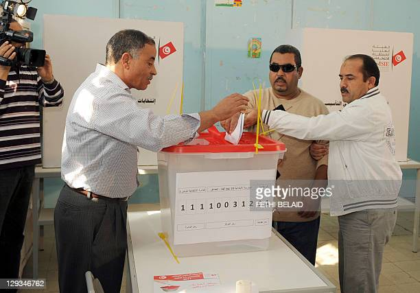 A man helps a blind man casting his vote as he takes part in a test vote at a polling station in Tunis on October 16 2011 Tunisia's electoral...