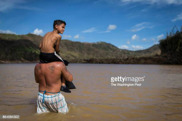 A man helps a kid cross the San Lorenzo River in Morovis Residents of San Lorenzo neighborhood can't access their houses because the river destroyed...