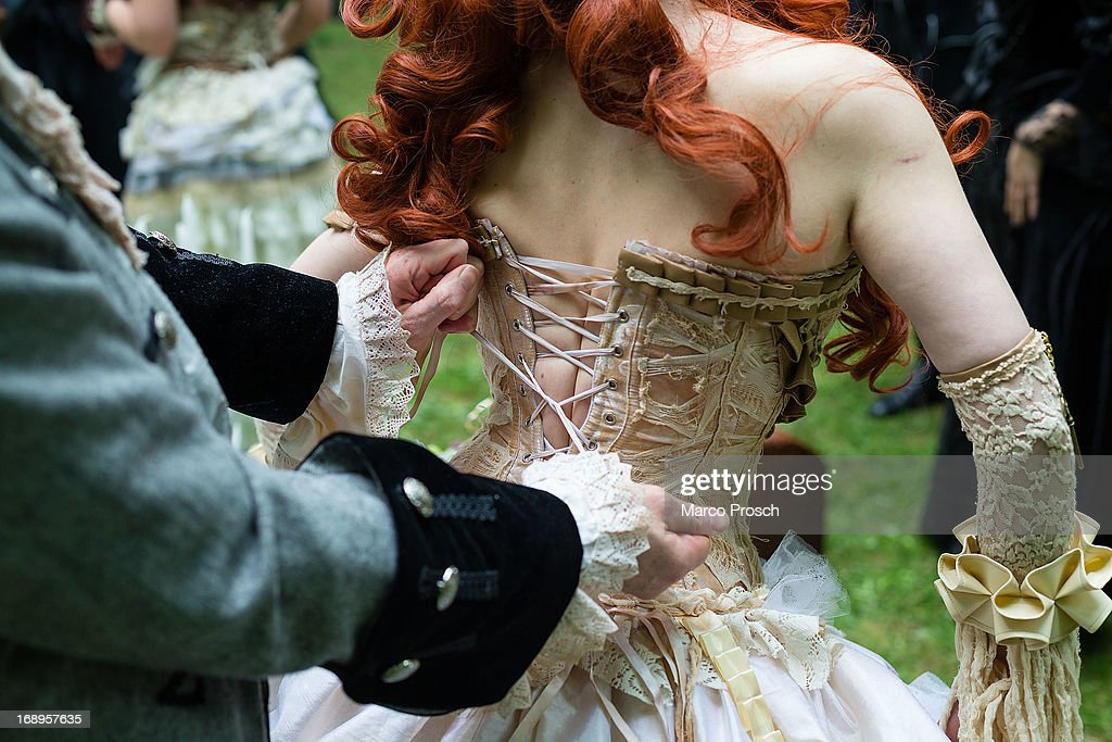 A man helps a woman straightening her corset during the traditional park picnic on the first day of the annual WaveGotik Treffen or Wave and Goth...