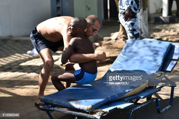 TOPSHOT A man helps a wounded child after heavily armed gunmen opened fire on March 13 2016 at a hotel in the Ivory Coast beach resort of GrandBassam...