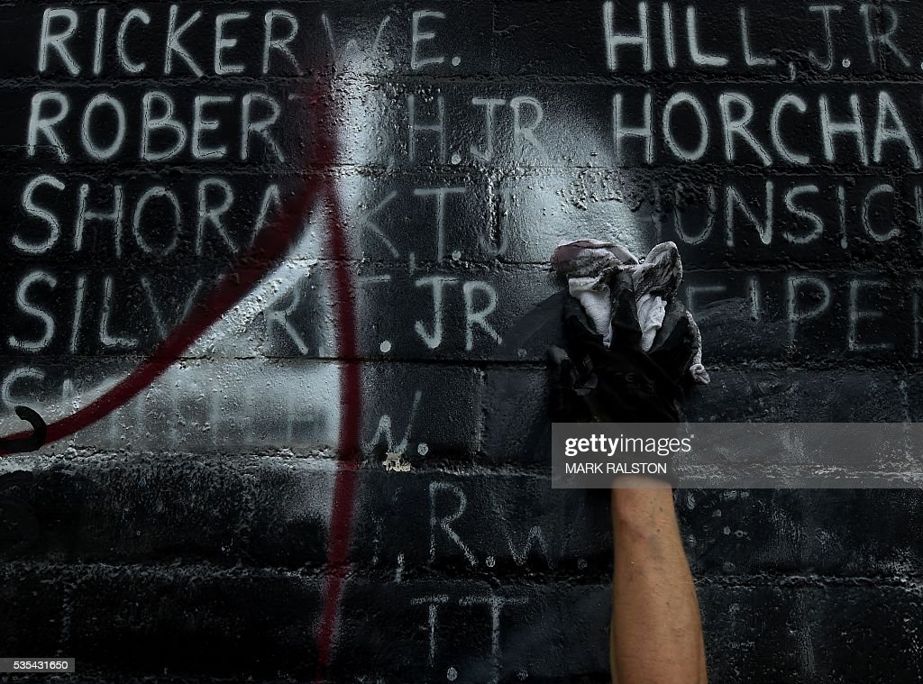 A man cleanups a Veterans Memorial containing the names of 2,273 unaccounted and missing in action (MIA) Vietnam war soldiers after vandals covered the mural with silver paint graffiti prior to Memorial Day in Venice Beach, California on May 29, 2016. / AFP / Mark Ralston