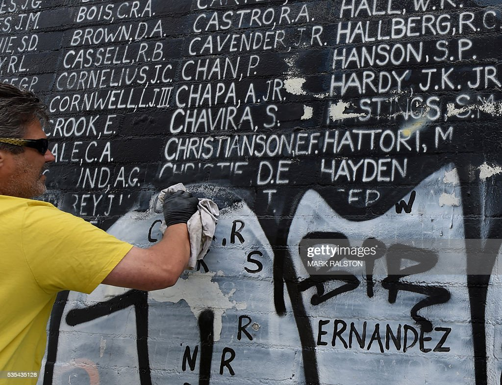 A man helps cleanup a Veterans Memorial containing the names of 2,273 unaccounted and missing in action (MIA) Vietnam war soldiers after vandals covered the mural with silver paint graffiti prior to Memorial Day in Venice Beach, California on May 29, 2016. / AFP / Mark Ralston