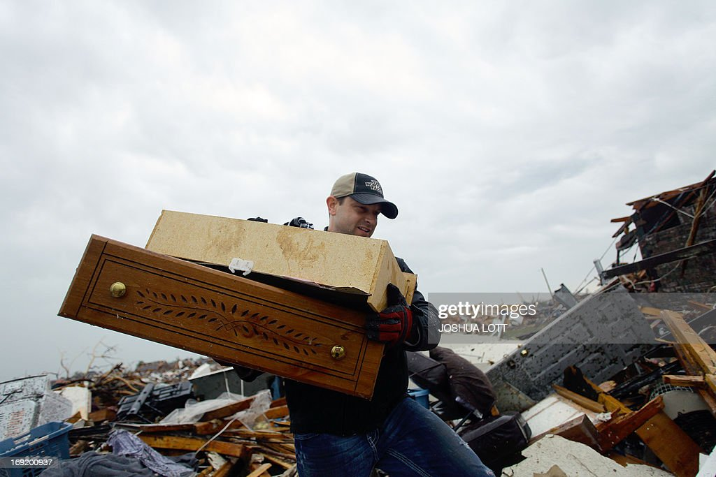 A man helps move a resident's belongings from a destroyed home on May 21, 2013 in Moore, Oklahoma. Families returned to a blasted moonscape that had been an American suburb Tuesday after a monstrous tornado tore through the outskirts of Oklahoma City, killing at least 24 people. Nine children were among the dead and entire neighborhoods vanished, with often the foundations being the only thing left of what used to be houses and cars tossed like toys and heaped in big piles. AFP PHOTO/Joshua LOTT