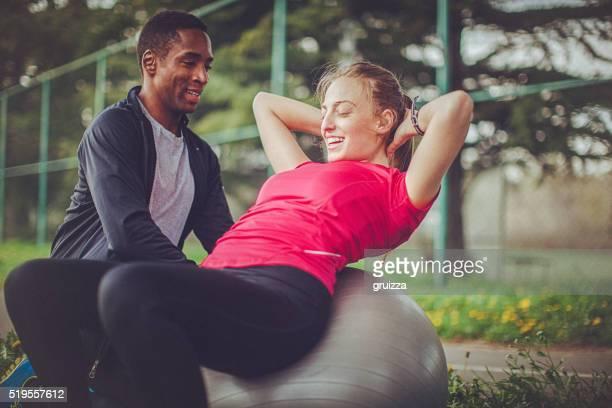 Mann hilft Frau zur korrekten Ausführung ab knirscht mit Kugel