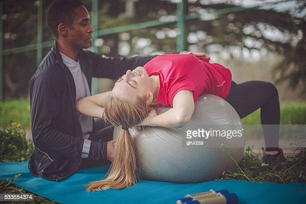 Man helps woman to correctly perform ab crunches on ball