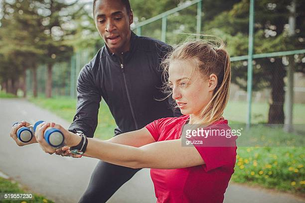 Man helps woman to correctly perform an exercise with dumbbells