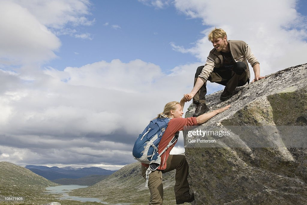Man helps woman up rocky outcrop : Stock Photo