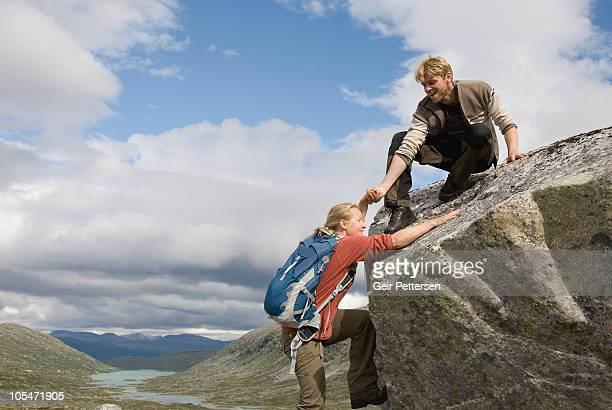 Man helps woman up rocky outcrop