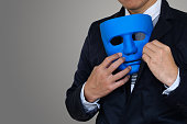 Businessman is hiding blue mask in your suit on gray background with clipping path and copy space