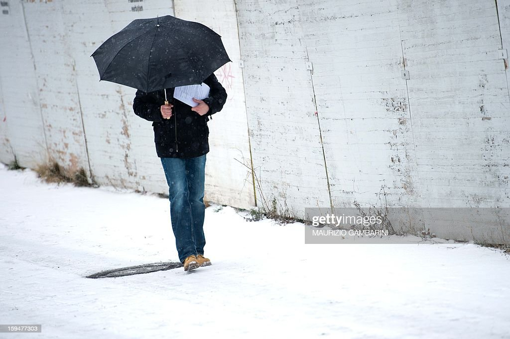 A man hides under an umbrella on January 14, 2013 in Berlin.