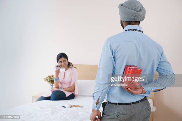 Man hiding a present from a woman