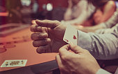 Close-up on a man hiding an ace under in his sleeve while playing poker at the casino