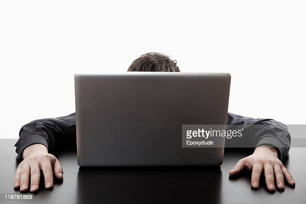 A man hiding behind a laptop