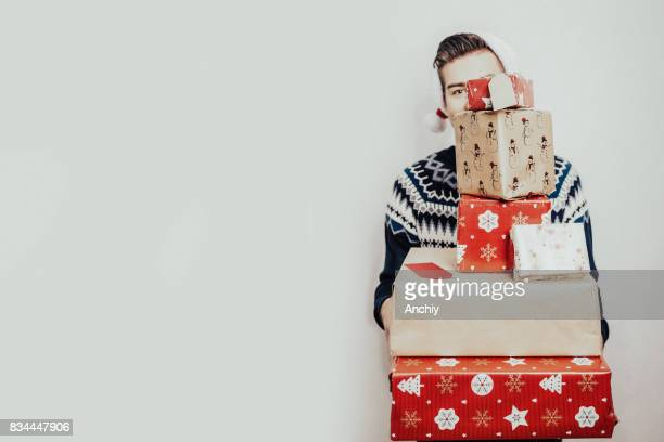 Man hiding behind Christmas gifts