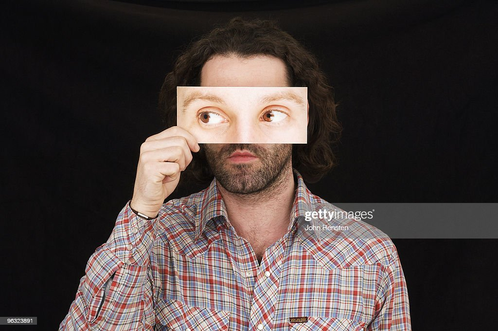 man hiding behind paper mask with false eyes  : Stock Photo