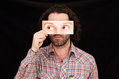 man hiding behind paper mask with false eyes