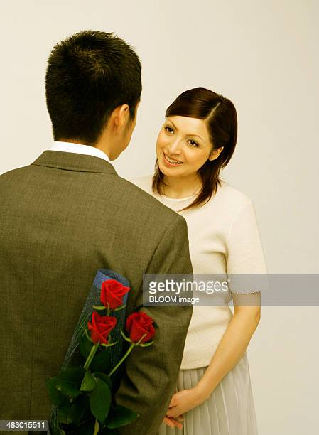 Man Hiding Bouquet From Woman