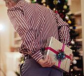 Man hiding christmas present behind back, rear view