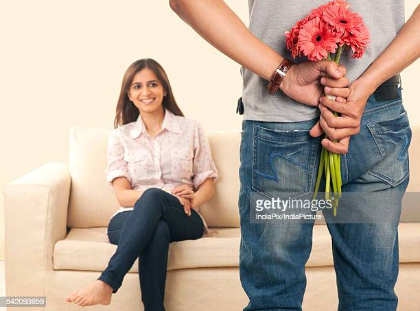 Man hiding flowers from his wife
