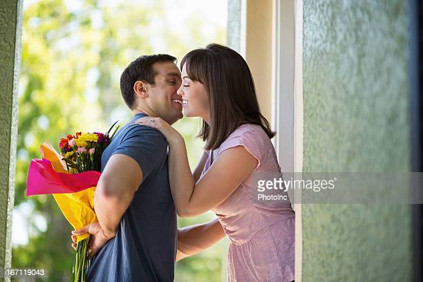 Man Hiding Flowers While Woman Embracing Him