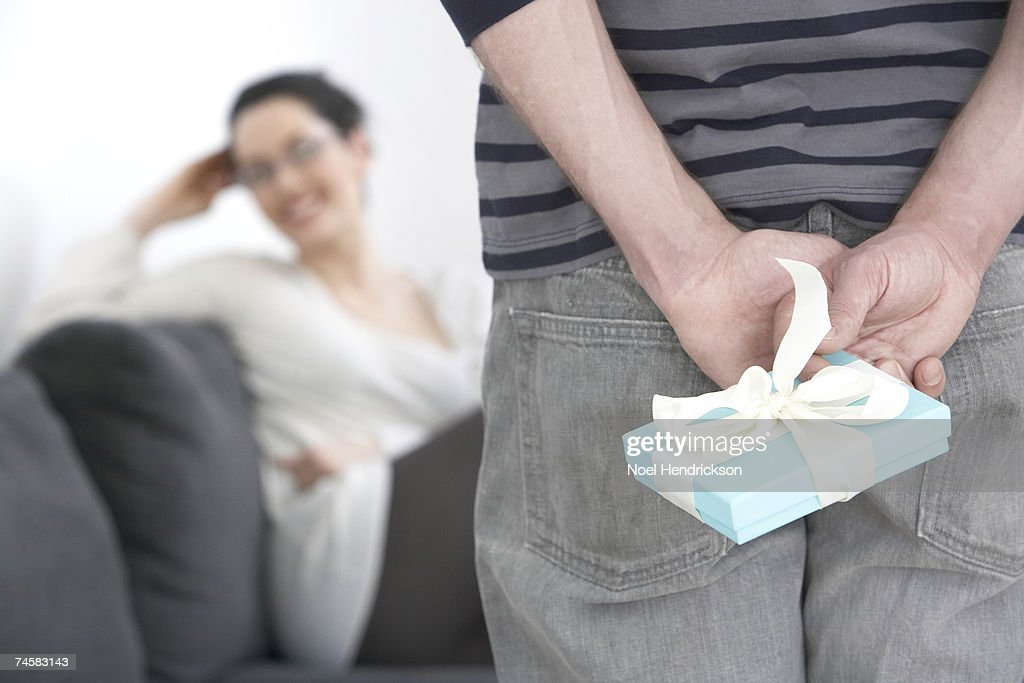 Man hiding gift behind back, mid section, woman in background : Stock Photo