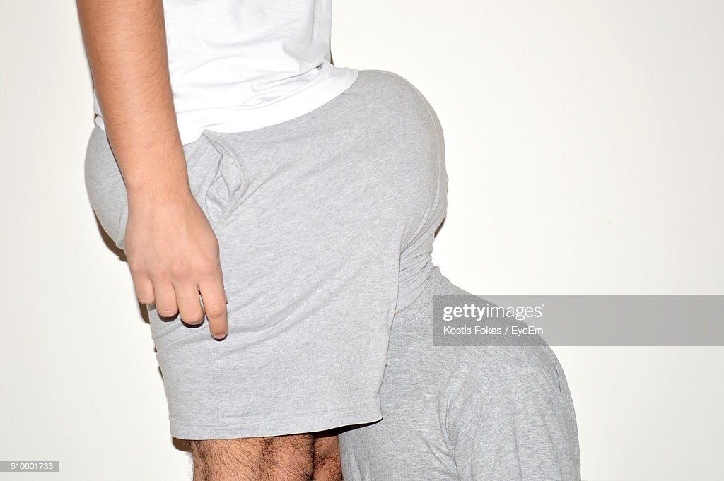 Man hiding head in boxer shorts of male friend