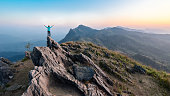 Man Hike on the peak of rocks mountain at sunset, active lifestyle, success concept.