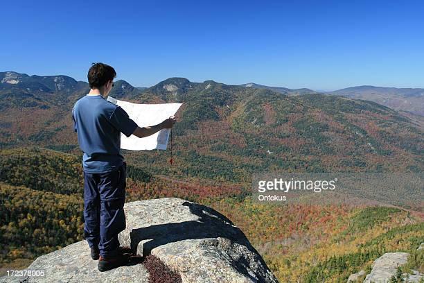 Mann Wanderer Blick auf Karte auf der Mountain Summit im Herbst