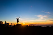 Man hiker silhouette with arms outstretched in mountains. Male runner or climber looking at sunset view. Business concept and hands up and enjoy inspirational landscape, rocky trail footpath on Teneri